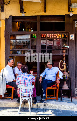 Greek Man Sit Chatting Outside A Cafe On Sokratous Street, Rhodes Old Town, Rhodes, Greece - Stock Photo