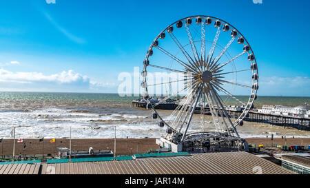 View of the Victorian Brighton Pier and the Brighton wheel in a windi day - Stock Photo