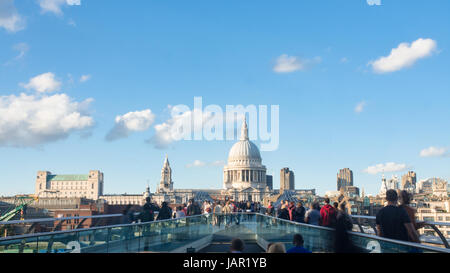 View of the Millennium bridge in London with St Paul cathedral and tourists and commuters walking - Stock Photo