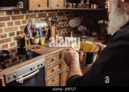 Man cooking spaghetti   - Stock Photo