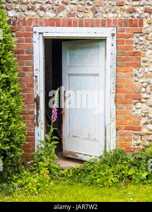 Old wooden doors in brick and flint walls in a a rustic garden in Norfolk, England. - Stock Photo