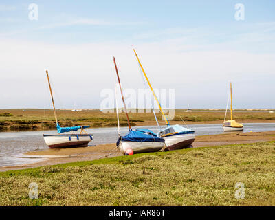 Small boats on the muddy shores of the New Cut channel through the salt marshes leading to Blakeney Quay in North - Stock Photo