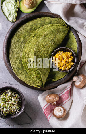 Green spinach matcha tortilla with vegan ingredients for filling. Sweet corn, avocado, green paprika, sprouts, mushrooms - Stock Photo