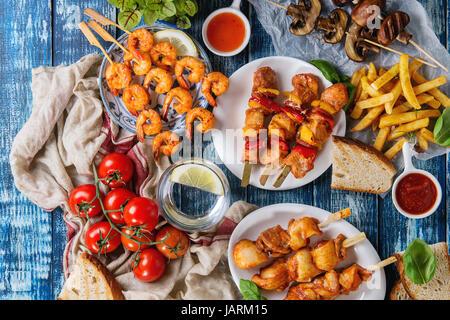 Variety of BBQ snack lunch. Plates grilled spicy prawn kebabs, chicken, pork, vegetables, mushrooms skewers, bread, - Stock Photo