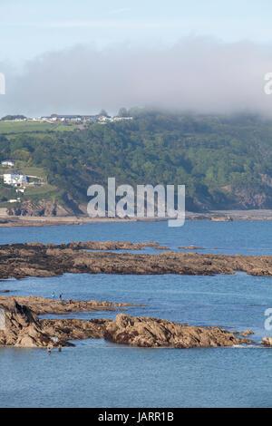 Sea mist rolls in over the coast at Looe, Cornwall - Stock Photo