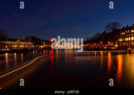 Trails of light on one of the major canals in Amsterdam at night - Stock Photo