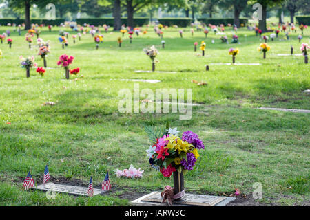 Gravesite floral decorations honoring the dead on Memorial Day in a cemetary in Wichita, Kansas, USA. - Stock Photo