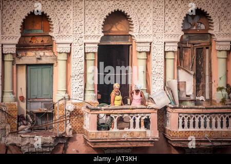 Two people talking on a balcony of an old building - Havana, Cuba - Stock Photo