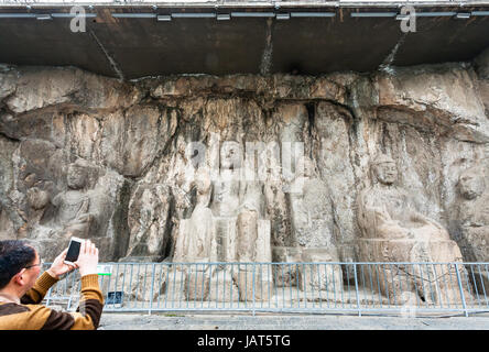 LUOYANG, CHINA - MARCH 20, 2017: tourist take photo of carved Buddha figure in Longmen Grottoes (Longmen Caves). - Stock Photo