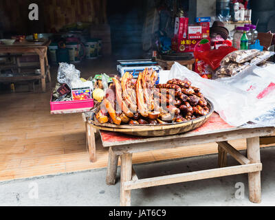 CHENGYANG, CHINA - MARCH 27, 2017: local smoked pork products in front of eatery in Chengyang village of Sanjiang - Stock Photo