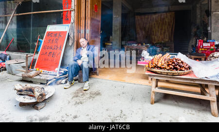 CHENGYANG, CHINA - MARCH 27, 2017: seller near local eatery and smokehouse in Chengyang village of Sanjiang Dong - Stock Photo