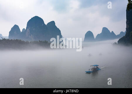 travel to China - view of fog with ships on river near Xingping town in Yangshuo county in spring morning - Stock Photo