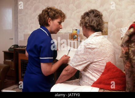 home help carers district nurse on a home visit to elderly woman in sheltered accommodation - Stock Photo