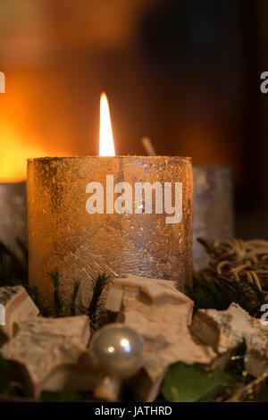 Brennende Kerze an einem Adventskranz - Stock Photo