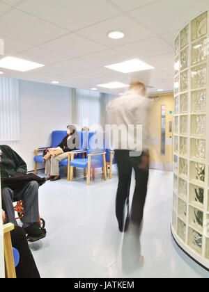 Patients sitting in NHS hospital waiting area, as a doctor walks through the frame, blurred through movement - Stock Photo