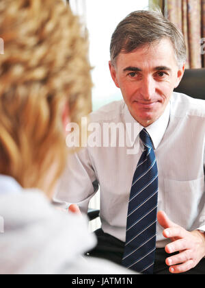 English white doctor (GP) is in a consultation with a middle aged lady at a NHS GP Surgery. The Doctor is explaining - Stock Photo