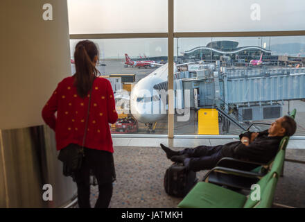 Hong Kong, China, 28th February 2015. two asian passengers waiting for their flight with a plane in the background - Stock Photo
