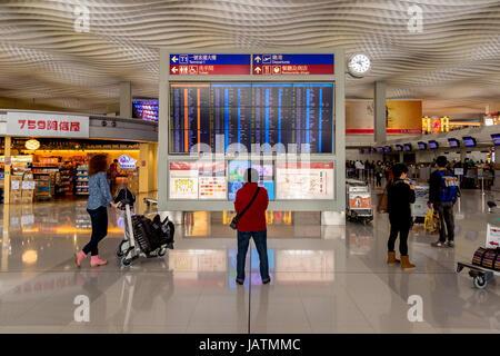 Hong Kong, China, 28th February 2015. Passenger looking at timetable board at Hong-Kong airport. - Stock Photo