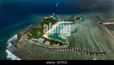 Small island in Maldives with typical resorts and bungallow on it. Picture was taken from plane. - Stock Photo