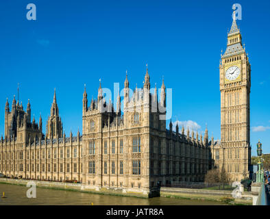 Bright blue sky morning view of Big Ben and the Houses of Parliament at Westminster Palace from the nearby bridge - Stock Photo