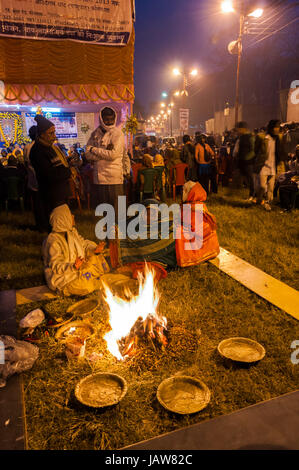 BABUGHAT, KOLKATA, WEST BENGAL / INDIA - 9TH JANUARY 2013 : Hindu devotees lighting a camp fire on 9th January, - Stock Photo