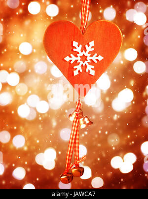 Beautiful red heart shaped Christmas decoration with snowflake ornament hanging on blur shiny background, stylish - Stock Photo