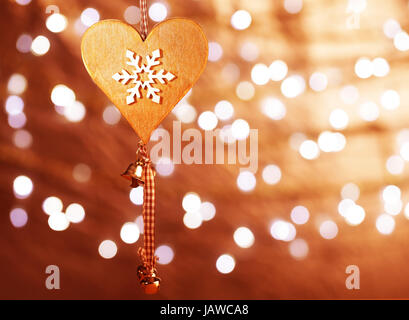 Beautiful wooden heart shaped New Year decoration with snowflake ornament hanging on blur shiny golden background, - Stock Photo