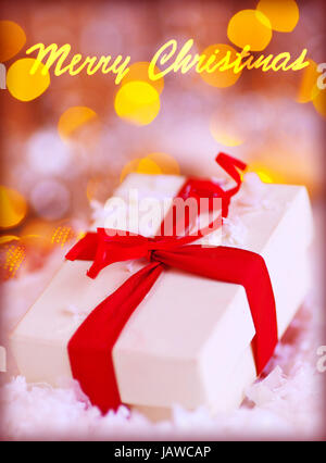 Closeup photo of little white gift box with red ribbon on blurry lights background, Merry Christmas greeting card, - Stock Photo