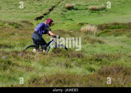 A female mountain biker makes her way across the rugged terrain at the Horseshoe Pass near Llangollen - Stock Photo