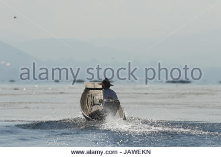 Rear view of fishermen on Inle lake in Myanmar. - Stock Photo