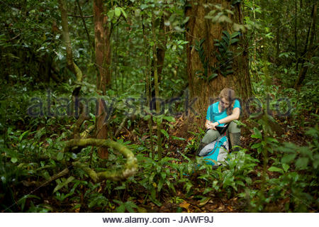 A girl sitting in the Borneo rain forest, writing in her notebook. - Stock Photo