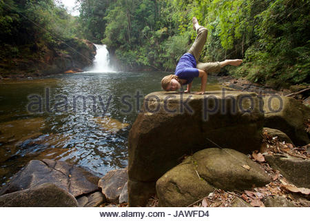 A girl practices yoga near Riam Berasap, the Falls of the Mists, which is the largest waterfall in Gunung Palung - Stock Photo