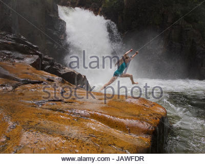 A girl leaps into the water below Riam Berasap, the Falls of the Mists, which is the largest waterfall in Gunung - Stock Photo