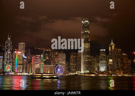 Light show on skyscrapers and Hong Kong Observation Wheel, reflected in Victoria Harbour, Central, Hong Kong Island, - Stock Photo