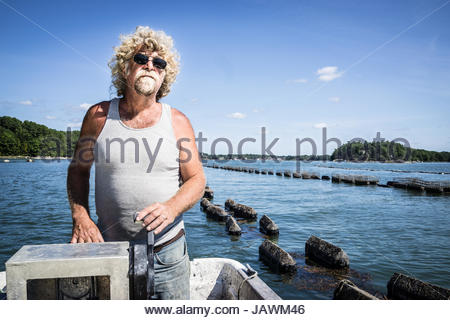 An oyster fisherman drives a boat down the river along his oyster beds. - Stock Photo