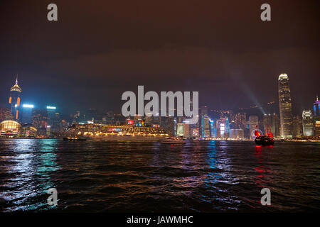 Victoria Harbour, cruse ship, junk, and light show on skyscrapers, Central, Hong Kong Island, Hong Kong, China - Stock Photo