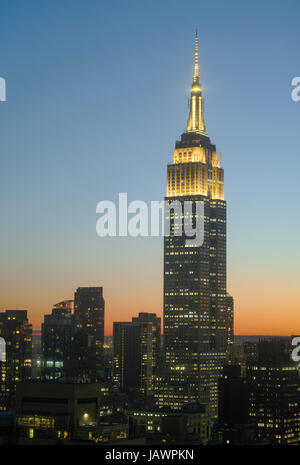 Empire State Building at sunset with yellow tower lights in honor of young artists and writers. Dark silhouettes - Stock Photo