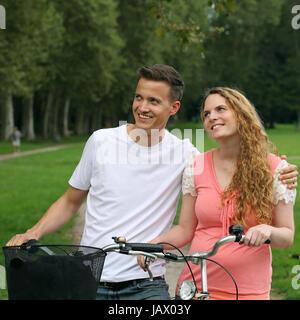 Eine junge Frau und ein junger Mann mit Fahrrädern haben ein Ziel vor Augen - Stock Photo