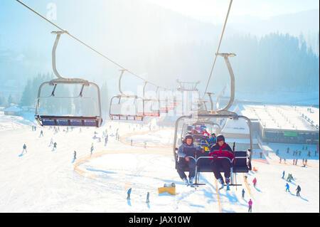Bukovel, Ukraine - December 13, 2013: Skiers on a ski-lift  in Bukovel. Bukovel - is the largest ski resort in Ukraine. - Stock Photo