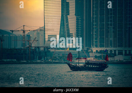 May 29, 2017 - Victoria Harbor, Hong Kong : Famous tour junk ship 'Aqualuna' crossing the Victoria Harbor with sunset - Stock Photo