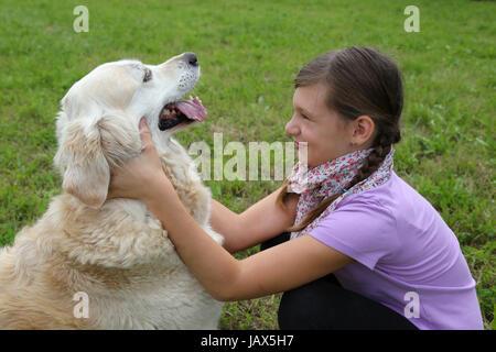Ein kleines Mädchen schmust mit einem Hund auf einer Wiese - Stock Photo