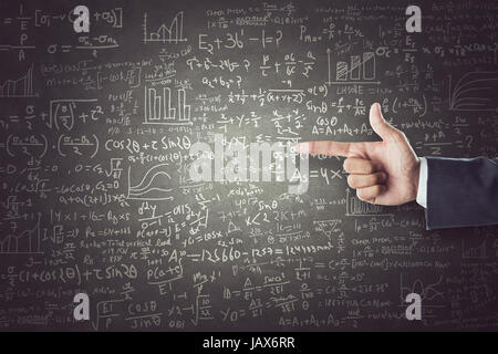 Women hand pointing sign in front of mathematical formulas drawn on blackboard - Stock Photo