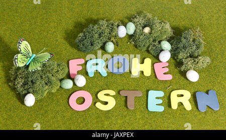 grass happy easter as text on green, decorated with moss and easter eggs - Stock Photo