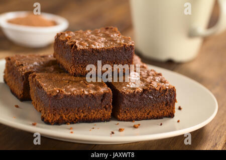 Freshly baked brownie pieces on a plate with cup in the back (Selective Focus, Focus on the left front part of the - Stock Photo
