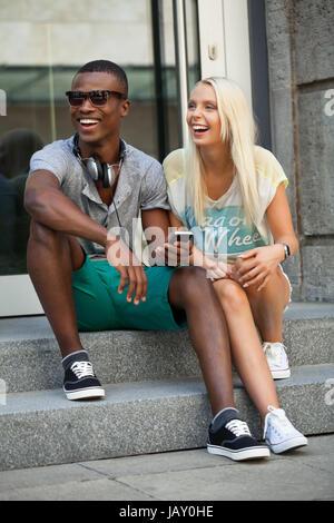 lachende junge freunde im sommer in der stadt mit mobiltelefon Stock Photo
