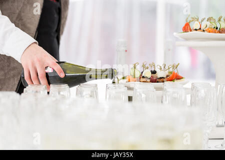 Waiter pours champagne in glasses - Stock Photo