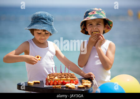 Sweet little children, twin boys, celebrating their sixth birthday on the beach, cake, balloons, candles, cookies. - Stock Photo