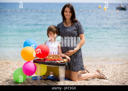 Sweet little child and his pregnant mom, celebrating his sixth birthday on the beach, cake, balloons, candles, cookies. - Stock Photo