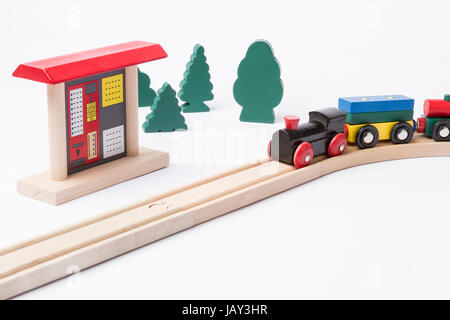 toy ticket machine at wooden railroad track with some trees in background - Stock Photo