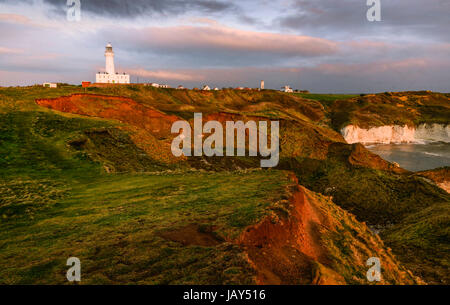 Weather and sea erosion along the north east coastline with view of lighthouse at sunrise in summer at Flamborough - Stock Photo